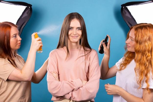 Studio fotografii niebieskie tło mistrzowska klasa dwóch rudowłosych fryzjerów naprawiających fryzurę młodej pięknej dziewczyny za pomocą dwóch lakierów do włosów salon kosmetyczny koncepcja profesjonalnego stylisty studiującego