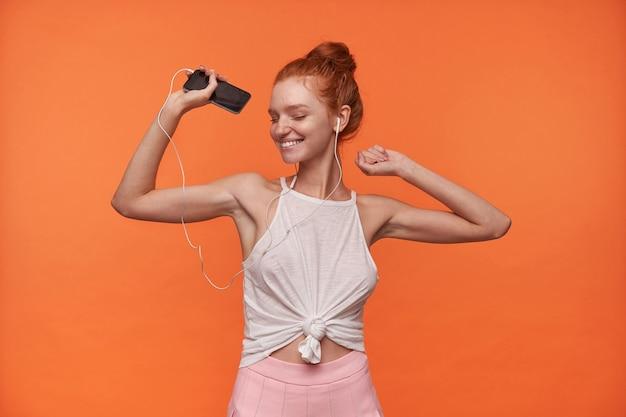 Studio fotografii uroczej młodej kobiety w rudych włosach w węzeł pozuje na pomarańczowym tle, słucha utworu muzycznego z zamkniętymi oczami, tańczy z uniesionymi rękami