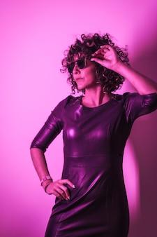 Studio lifestyle, młoda kobieta rasy kaukaskiej, ciesząca się sesją w eleganckich ubraniach i okularach przeciwsłonecznych z neonowym różowym światłem