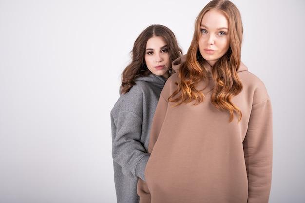 Studio moda portret dwóch eleganckich młodych kobiet w stylowych bluzach pozujących modne dziewczyny w modnych garniturach jasny makijaż, monochromatyczne ubrania. koncepcja mody i stylu.