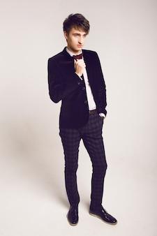 Studio moda portret przystojnych mężczyzn w stylowym luksusowym garniturze i muszce, jasnym tle, delikatnych kolorach.