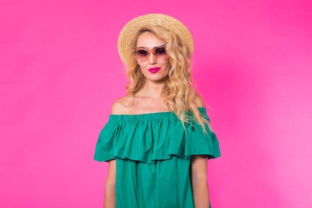 Studio mody portret glamour dziewczyny, stylowe ubrania okulary na różowym tle z