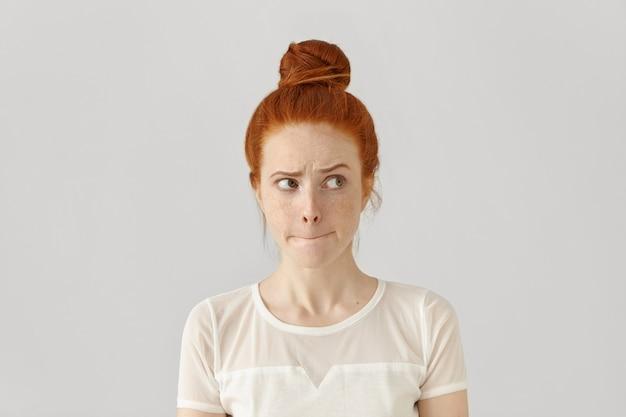Studio na białym tle strzał wątpiący w zakłopotaną kobietę z piegowatą śliczną młodą rudą, patrząc w bok