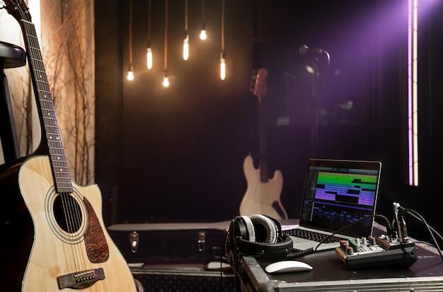 Studio nagrań tło z gitarą akustyczną, laptopem, mikserem dźwięku i słuchawkami na stole. miękkie światło lampy na ciemnym tle.