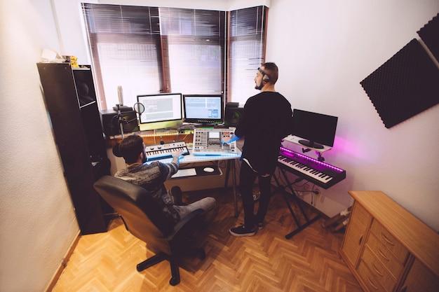 Studio nagrań ze sprzętem muzycznym i operatorami konsol.