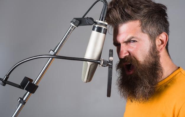 Studio nagrywa brodaty mężczyzna śpiewa do mikrofonu karaoke mężczyzna śpiewa z mikrofonem śpiewa w