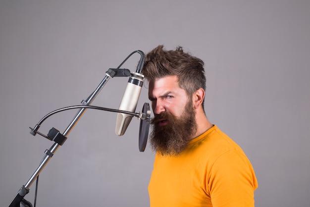 Studio nagrywa brodaty mężczyzna śpiewa w mikrofonie mikrofon śpiewa piosenkę karaoke mężczyzna śpiewa z