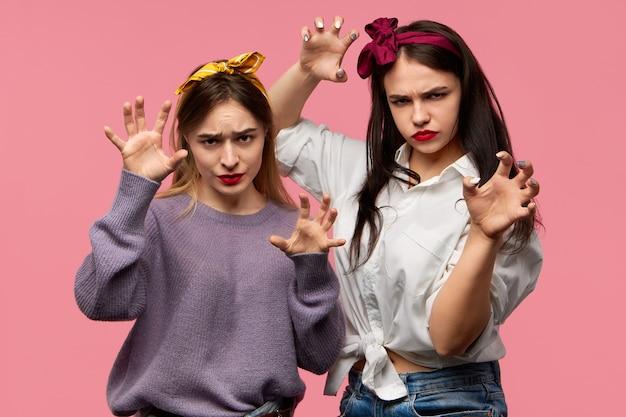 Studio obraz dwóch atrakcyjnych emocjonalnie młodych kobiet zachowujących się agresywnie, grymasujących z dzikim przerażającym wyrazem twarzy, robiącym gest próbujący cię przestraszyć. ludzkie emocje, uczucia i reakcje