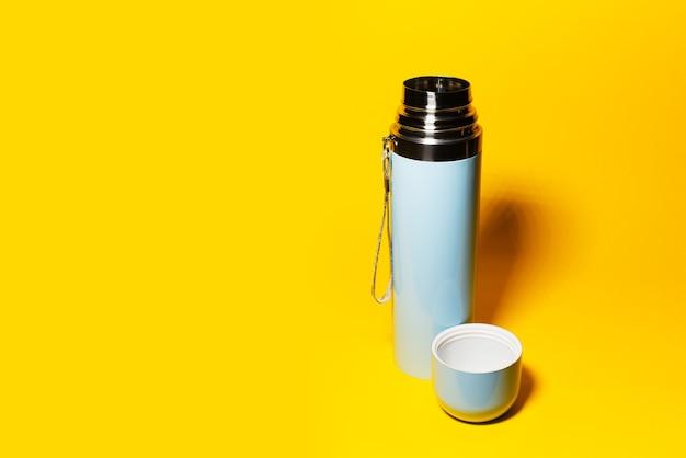 Studio obraz jasnoniebieskiego termosu z nasadką w kolorze żółtym z miejscem na kopię.