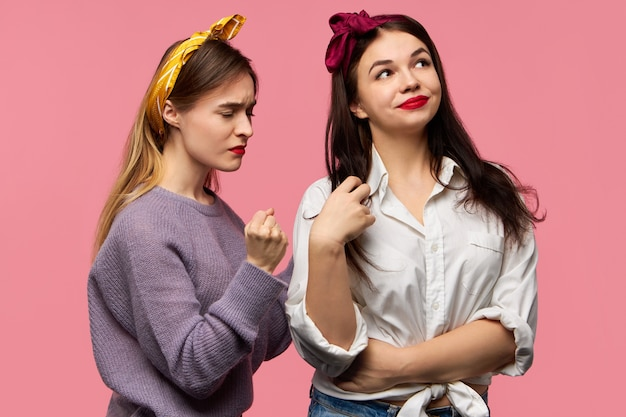 Studio obraz wściekłej, szalonej młodej kobiety rasy kaukaskiej, która traci panowanie nad sobą, będąc zła na swoją wredną przyjaciółkę, która w ogóle się tym nie przejmuje. dwie kobiety wyrażające różne emocje, pozowanie na białym tle
