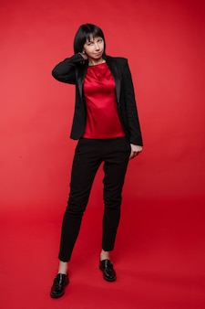 Studio portret atrakcyjnej bizneswoman uśmiechający się na sobie elegancki czarny garnitur z spodnie i oksfordki. ona trzyma ręce złożone na czerwonym tle.