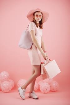 Studio portret całkiem młoda kobieta stojąca z papierowymi workami z balonami w tle