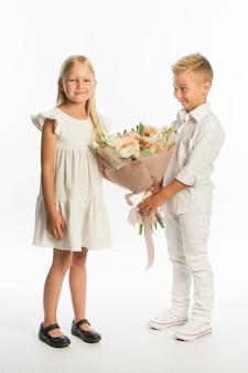 Studio portret chłopca daje dziewczynie świąteczny bukiet, gratulacyjna koncepcja, białe tło, kopia przestrzeń