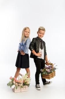 Studio portret chłopca i dziewczynki ubrani w mundurek szkolny z pozdrowieniami kwiatowymi w drewnianych koszach, koncepcja gratulacyjna, białe tło, miejsce na kopię
