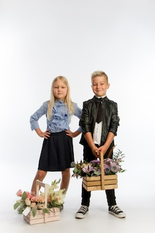 Studio portret chłopca i dziewczynki ubrani w mundurek szkolny z pozdrowieniami kwiatowymi w drewnianych koszach, koncepcja gratulacyjna,