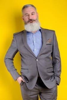 Studio portret dojrzały brodaty mężczyzna w szarym garniturze, patrząc na kamery, styl życia zawód pracy, żółte tło.