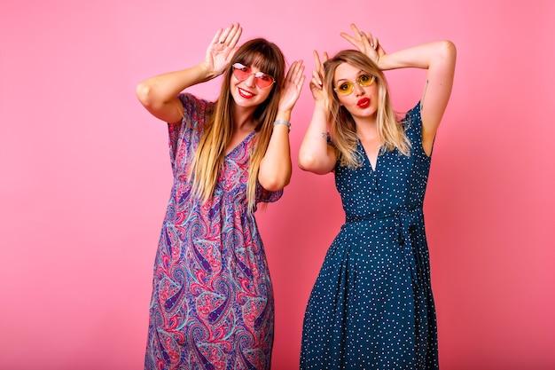 Studio portret dwóch pozytywnych najlepszych przyjaciół kobiet zabawy na różowym tle