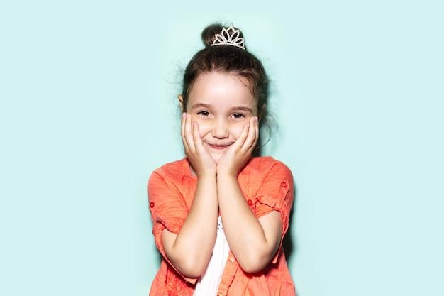 Studio portret dziecka dziewczyna w koralowej koszuli, trzymając dłonie na policzkach