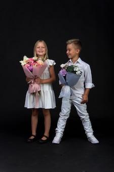 Studio portret dziewczyny i chłopca z bukietami, gratulacyjna koncepcja, czarne tło, kopia przestrzeń
