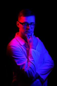 Studio portret lekarza lub specjalisty medycznego. stojąc z ramieniem blisko twarzy. mężczyzna w zaroślach. czarne tło z niebieskim i czerwonym światłem. zbliżenie.