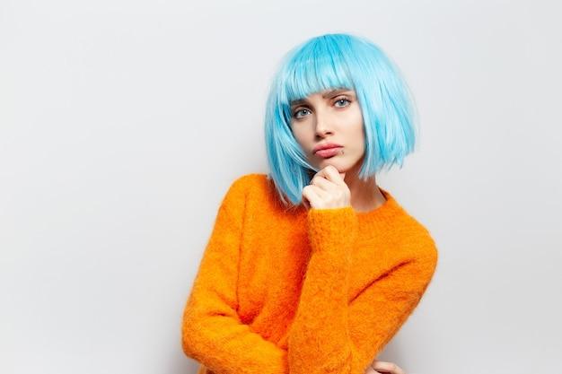 Studio portret młodej dziewczyny słodkie starając się być poważnym, na tle białego, ubrana w niebieską perukę i pomarańczowy sweter.