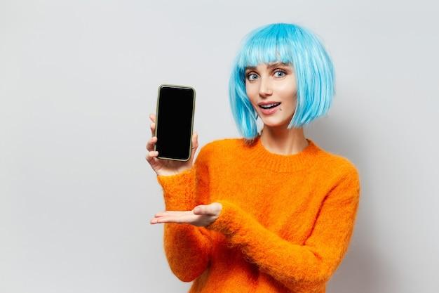 Studio portret młodej dziewczyny szczęśliwy wyświetlono na smartfonie, na sobie perukę niebieskie włosy i pomarańczowy sweter na białym tle.