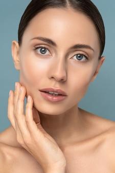 Studio portret młodej kobiety z naturalnym makijażem, czesanymi włosami, dotykającymi jej zadbanej, czystej skóry
