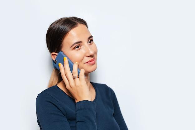 Studio portret młodej uśmiechnięta brunetka kobieta rozmawia na smartfonie