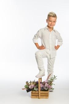 Studio portret modnego blond kaukaski chłopca z drewnianym koszem kwiatów, białe tło, miejsce
