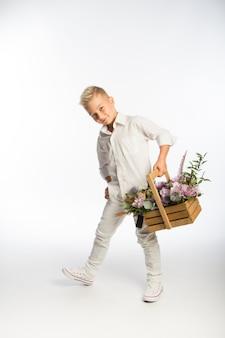 Studio portret modnego blond kaukaskiego chłopca z drewnianym koszem kwiatów, białą ścianą, miejscem na kopię