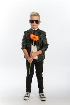 Studio portret modnej blond kaukaski chłopca z pojedynczym kwiatem gerbera