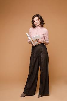 Studio portret modnej kobiety brunetka w odzieży casual, trzymając w ręku otwartą książkę i czytając. pełna długość stock photo izolować na tle.