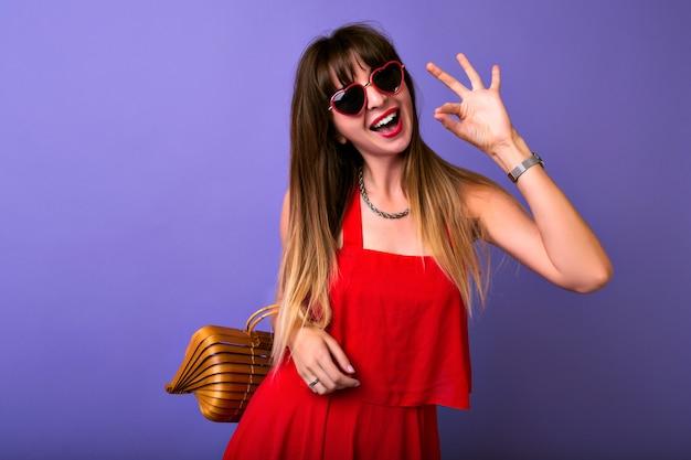 Studio portret pięknej modnej brunetki na sobie elegancką czerwoną sukienkę letnią, okulary przeciwsłoneczne herat, drewnianą torbę.