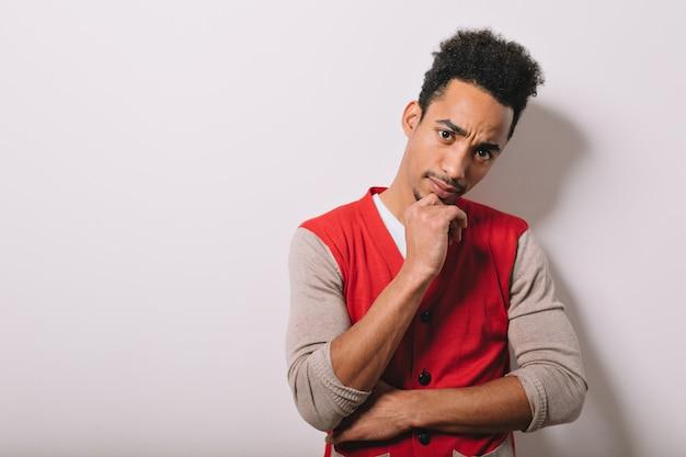 Studio portret poważnego czarnego amerykańskiego mężczyzny ubranego w czerwoną koszulę na szaro