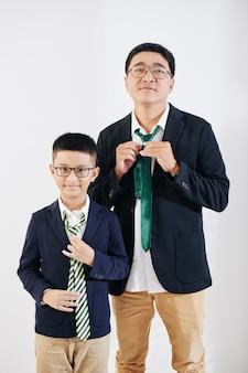 Studio portret pozytywnego dojrzałego mężczyzny i jego syna-animatora dopasowujących krawaty, przygotowując się do imprezy