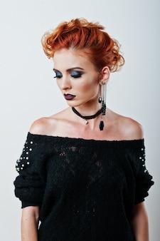 Studio portret rudowłosej dziewczyny na czarnej bluzce i jeansowych spodenkach z jasnym ciemnym makijażem