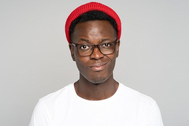 Studio portret sceptyczny afro hipster nosić okulary z fałszywym uśmiechem, niestety patrząc na kamery, na białym tle szarym tle. zdenerwowany czarny facet stara się zachować pozytywne nastawienie po niepowodzeniu.