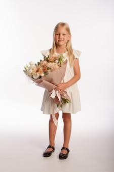 Studio portret śliczna blondynka w białej sukni z drewnianym koszem kwiatów, biała ściana, selektywna ostrość