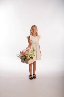 Studio portret śliczna blondynka w białej sukni z drewnianym koszem kwiatów, białe tło, selektywna ostrość