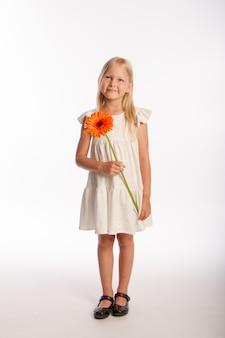 Studio portret śliczna blondynka w białej sukni z pojedynczym kwiatem gerbera, białe tło, selektywna ostrość