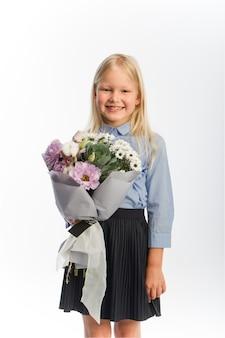 Studio portret śliczna blondynka w mundurku szkolnym z pięknym bukietem prezentów, selektywne focus