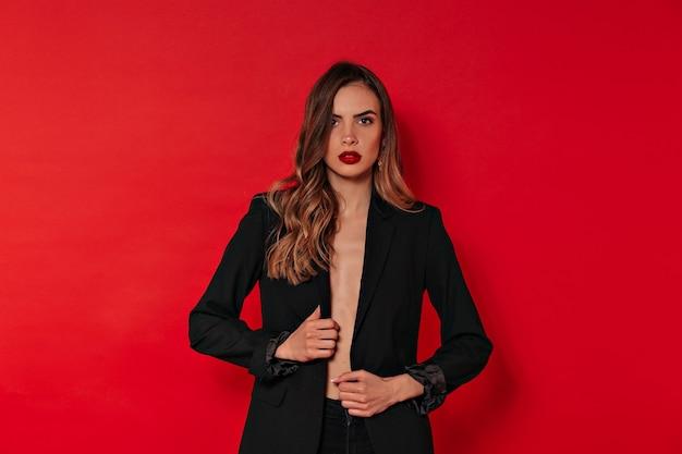 Studio portret spektakularnej stylowej kobiety w czerni z czerwonymi ustami i świętującej walentynki