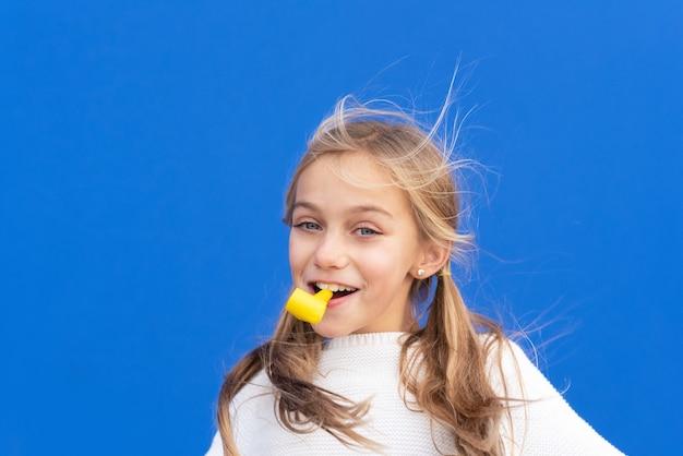 Studio portret szczęśliwej, uśmiechniętej młodej dziewczyny z okazji urodzin, trzymając w ustach dmuchawę, odizolowane na niebiesko.