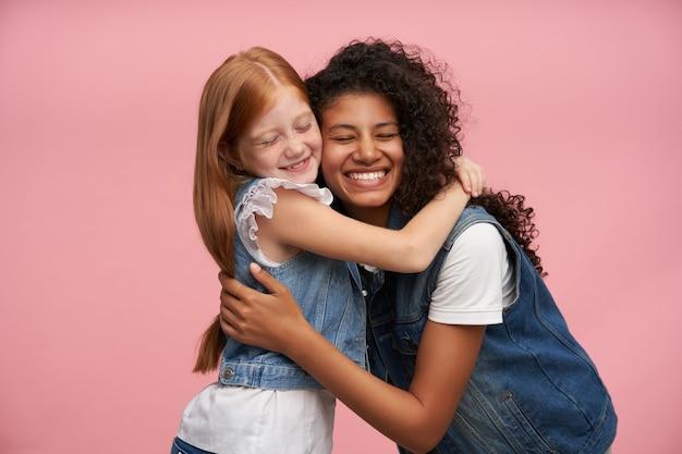 Studio portret szczęśliwych uroczych dziewczyn cieszących się delikatnymi uściskami, pozując na różowo, uśmiechając się wesoło i mając zamknięte oczy, w dżinsowych kamizelkach i białych koszulach