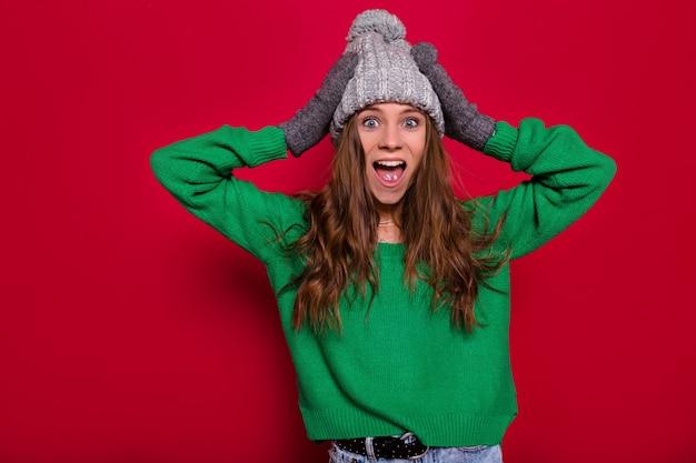 Studio portret uroczej wychodzącej szczęśliwej kobiety z długimi jasnobrązowymi włosami na sobie zielony sweter i szarą czapkę zimową, pozowanie w aparacie z otwartymi ustami i trzyma ręce, na białym tle