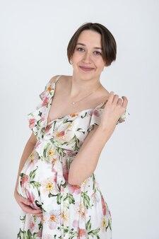 Studio portret wesoła młoda kobieta w ciąży w letniej sukience na białej szarej ścianie, koncepcja szczęśliwej ciąży