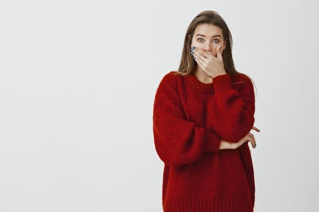Studio portret zszokowanej, zdziwionej atrakcyjnej kobiety w luźnym swetrze, zakrywającej otwarte usta dłonią i gapiącej się przerażonej, zdziwionej i zaskoczonej