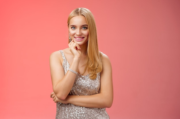 Studio shot atrakcyjna radosna delikatna blond europejska kobieta w eleganckiej srebrnej błyszczącej sukience dotknij podbródka uśmiechnięty zainteresowany słuchanie rozmowy przyjaciela podczas imprezy, czerwone tło.
