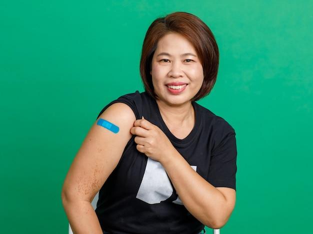 Studio shot azjatycka pacjentka w średnim wieku siedzi uśmiechać się patrzeć na kamery pokazać niebieski bandaż gipsowy na ramieniu po otrzymaniu szczepienia na koronawirusa covid 19 od lekarza w szpitalu na zielonym tle.