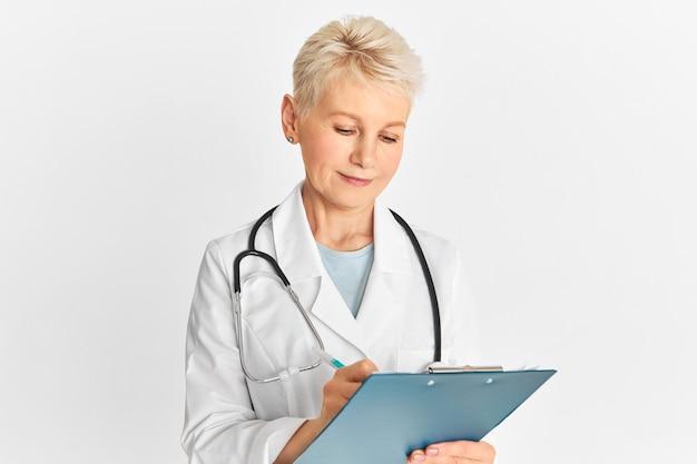 Studio strzał atrakcyjnej blondynki w średnim wieku lekarz ze stetoskopem na szyi, pozowanie na białym tle za pomocą pióra i schowka, sporządzenie dokumentacji medycznej, przepisanie leczenia dla pacjenta